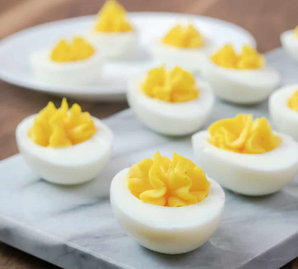 Deviled eggs on marble serving board.