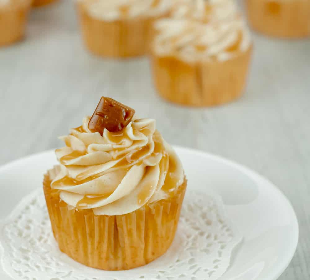 Homemade caramel drizzled on brown sugar buttercream frosting with a vanilla cupcake base on a white plate.