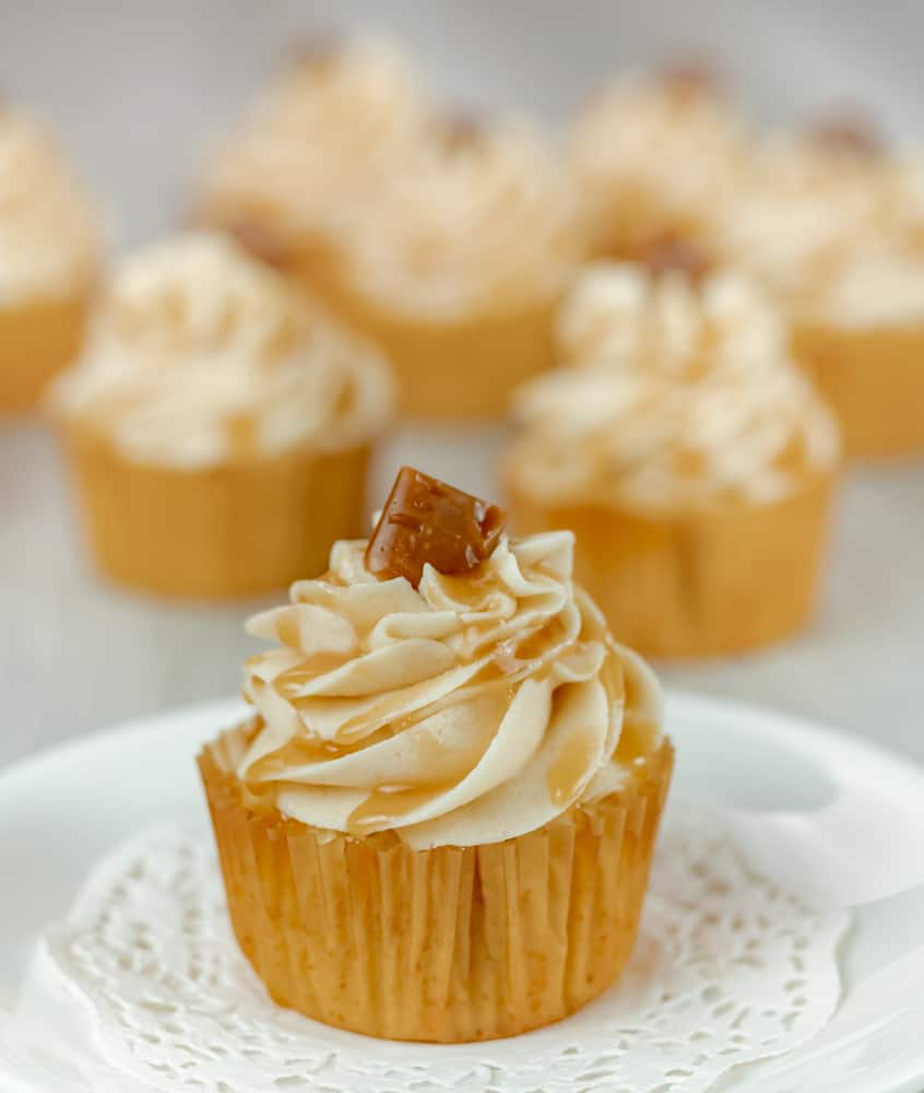 Homemade caramel drizzled on brown sugar buttercream frosting with a vanilla cupcake base in brown cupcake liner.