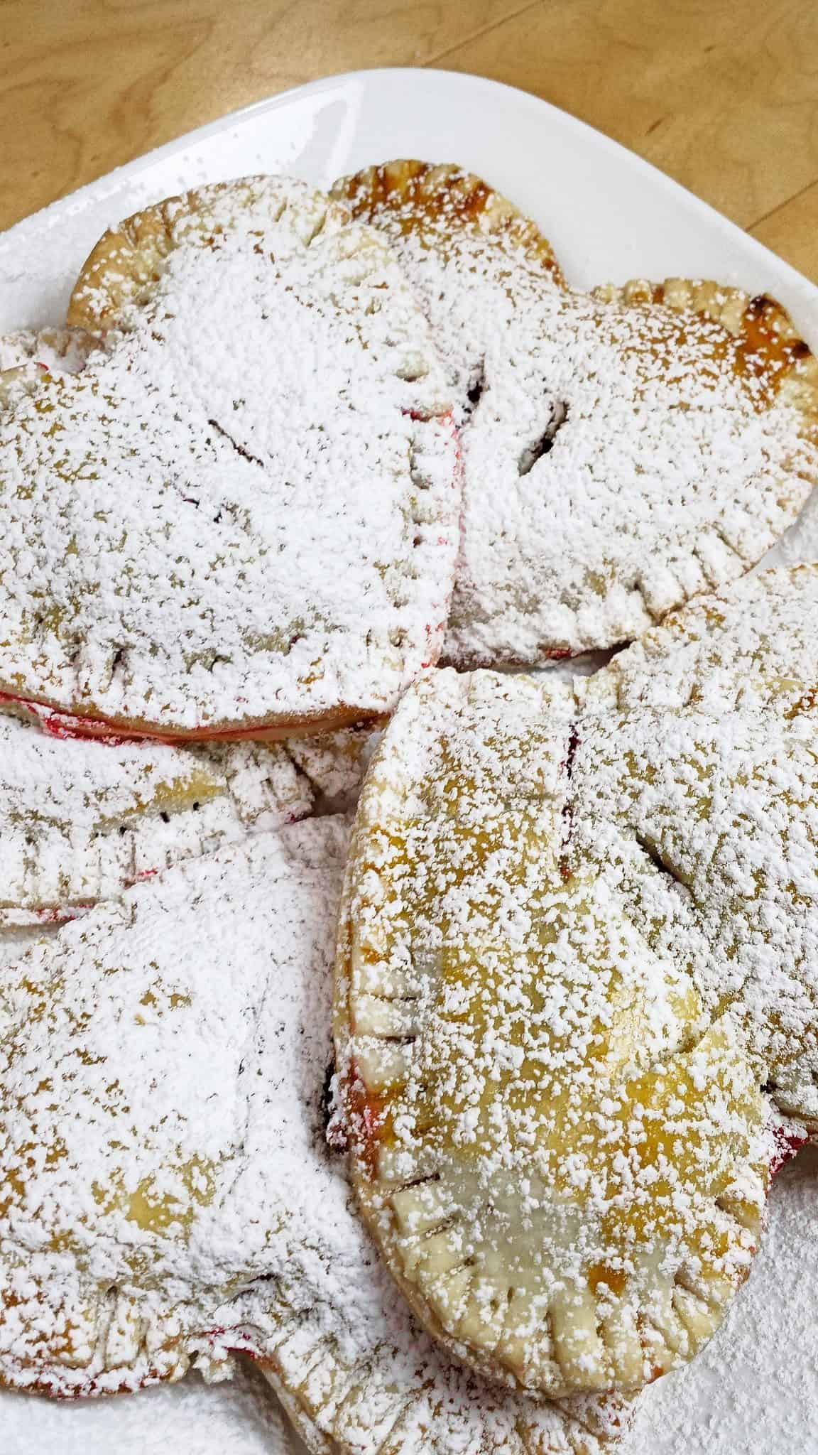 A plate of cherry hand pies that are heart shaped dusted with confectioner's sugar.