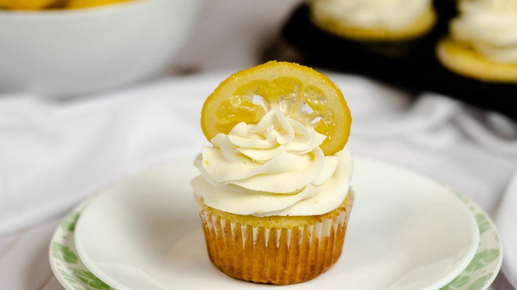 A plate with a lemon vanilla cupcake topped with frosting and garnished with a candied lemon.
