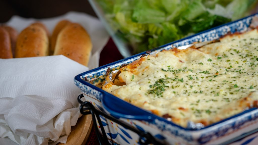 A 13x9 baking dish with homemade cheesy lasagna with a sleeve of breadsticks in the background.