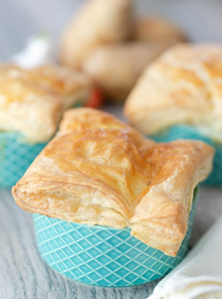 Flaky puff pastry square sitting on top of a ramekin of Chicken Pot Pie.