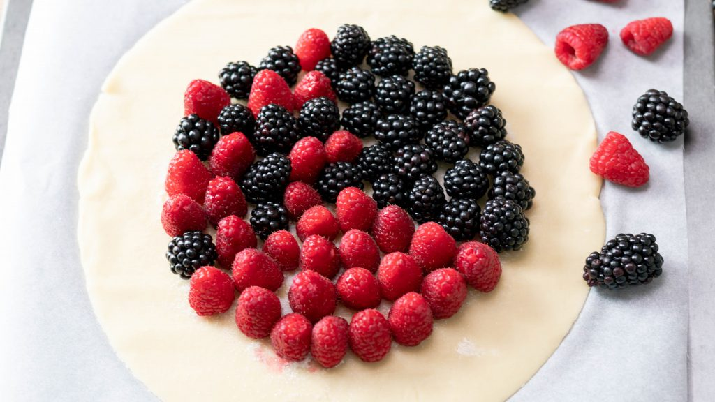 Raspberries and blackberries on a pie crust unfolded and before baking.