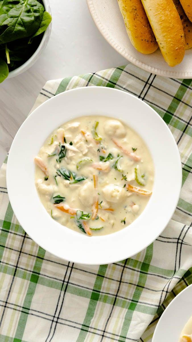A bowl of Olive Garden Chicken Gnocchi Soup copycat on a green checkered napkin.