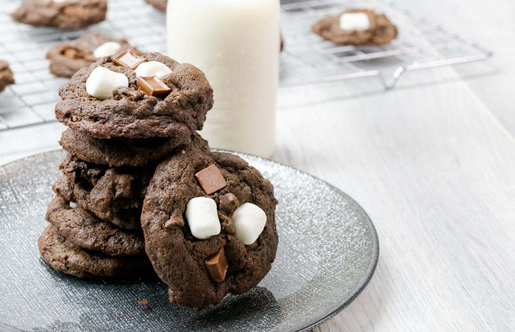 hot cocoa cookies hot chocolate mix mini marshmallows chocolate chunks glass of milk black plate baker's rack