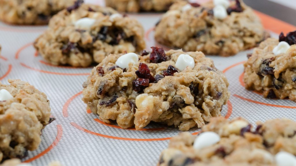 cranberry white chocolate chip oatmeal cookies gray background soft and chewy silicone mat