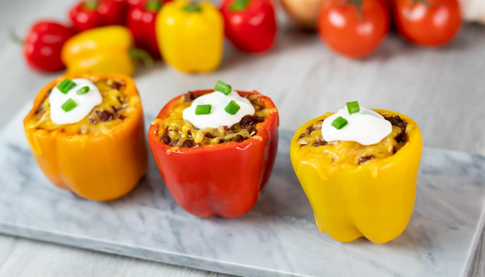 homemade chili stuffed orange red yellow peppers cream cheese onions marble serving board gray background peppers in background