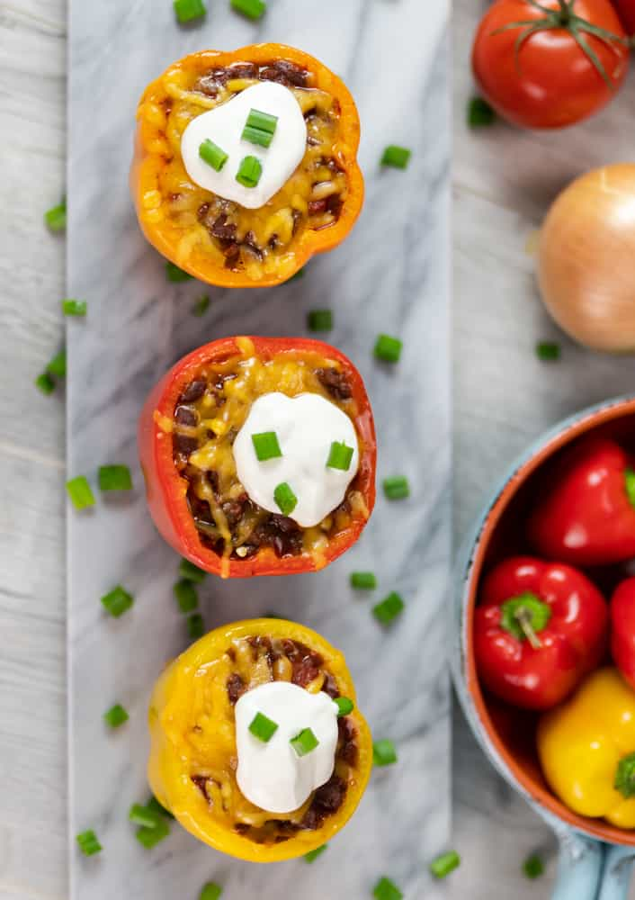 homemade chili stuffed peppers with orange red yellow peppers cream cheese onions marble serving board gray background peppers in background peppers in bowl