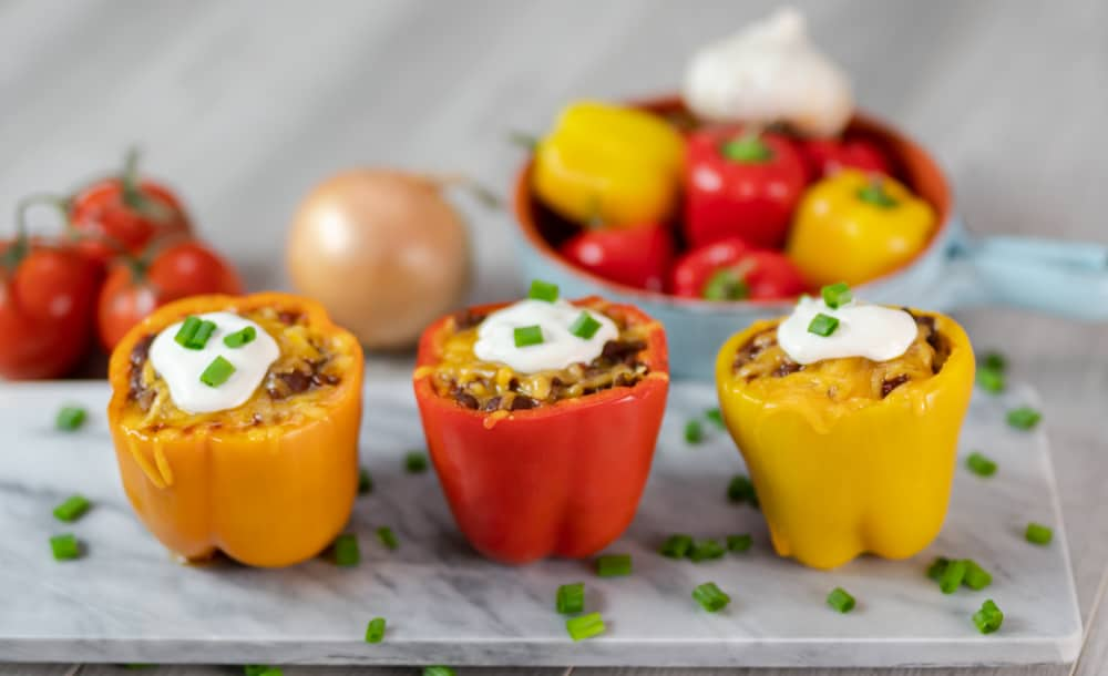 homemade chili stuffed orange red yellow peppers cream cheese onions marble serving board gray background peppers in background peppers in bowl