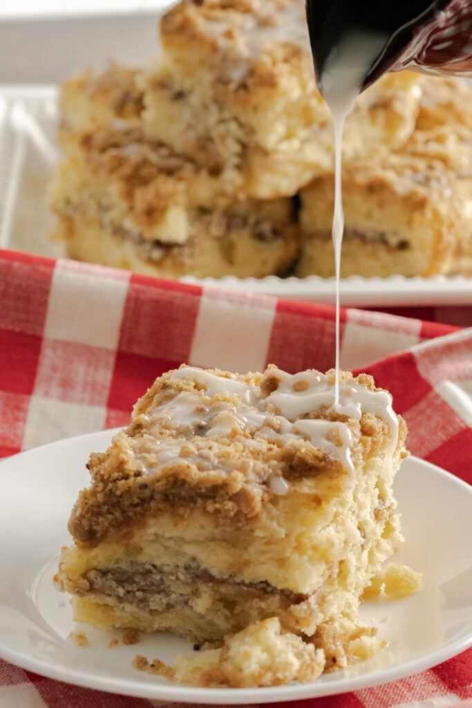 A slice of sour cream coffee cake with icing being drizzled on it.