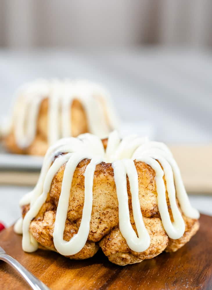 mini bundt cinnamon sugar pull-apart bread with cream cheese glaze serving board fork with rose red napkin
