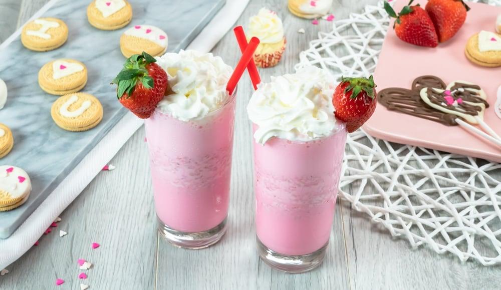 strawberry ice cream milkshake with whipped cream and fresh strawberry garnish chocolate dipped cookies and heart chocolates pink and white sprinkles