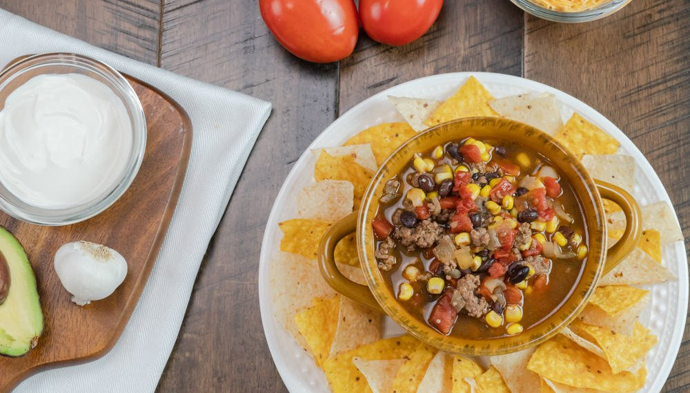 instant pot taco soup in brown bowl with handles topped with shredded cheese and fresh diced avocado fresh tomatoes and sour cream in back ground. white and yellow tortilla chips