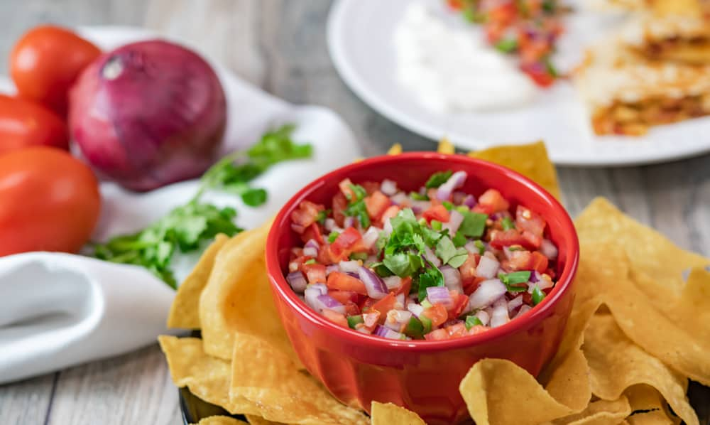 Fresh pico de gallo with fresh baked tortilla chips and gray background.