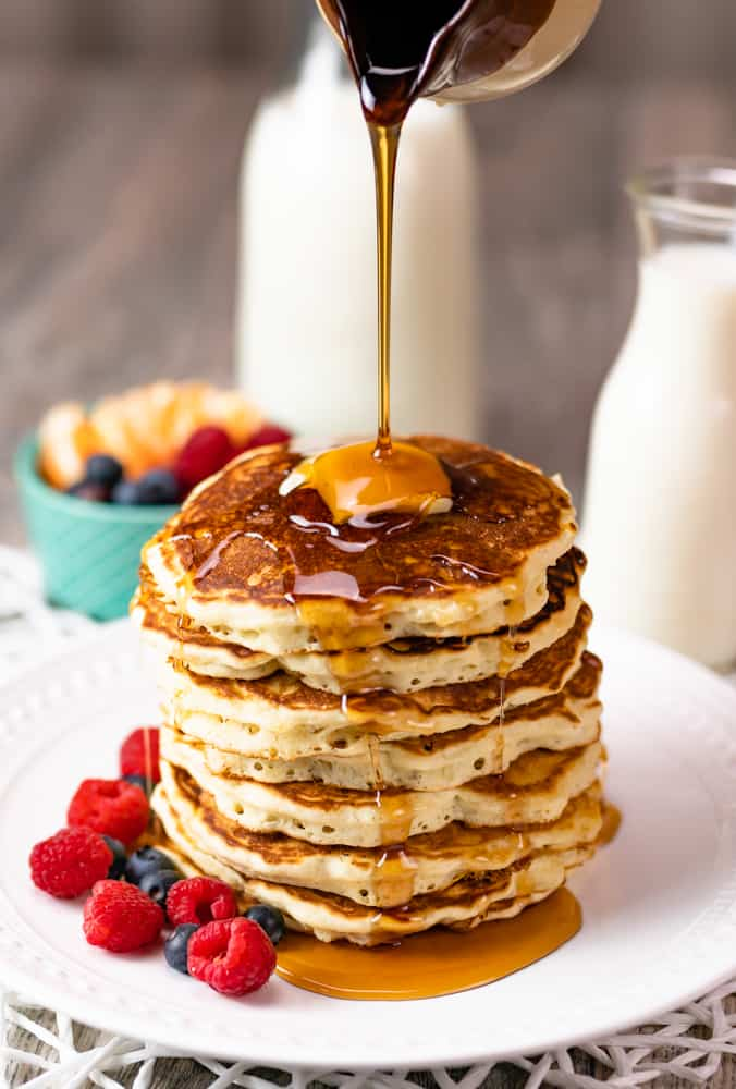 Brown butter pancakes stacked with a pat of butter and poured syrup.