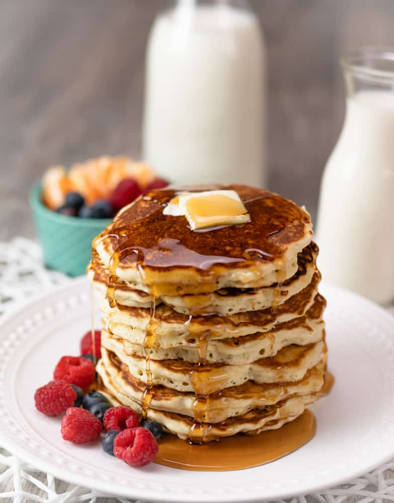 Brown butter pancakes with butter and syrup.  Raspberries and blueberries on the side.