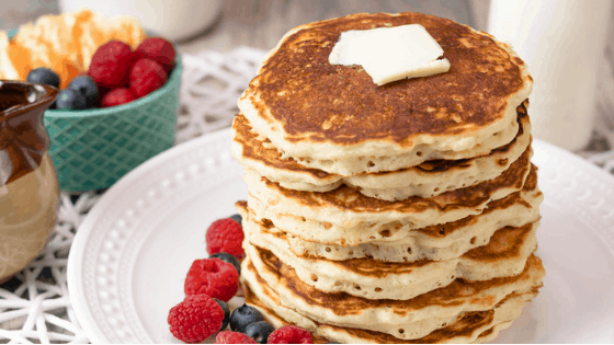 easy brown butter pancakes topped with sliced butter and served with raspberries and blueberries.