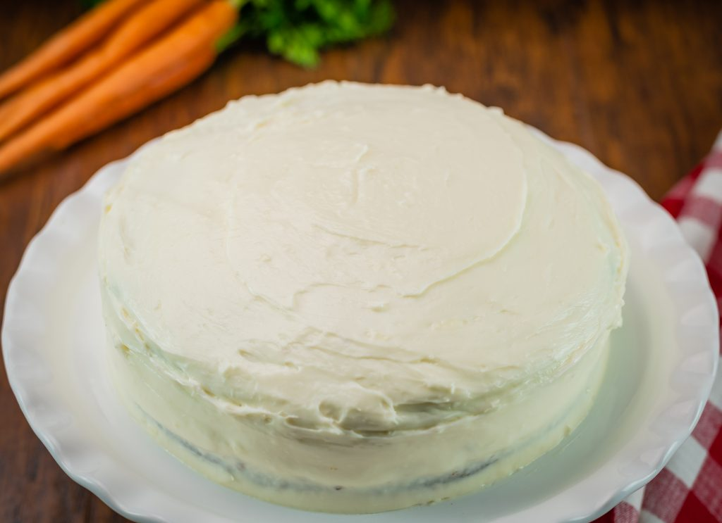 A whole homemade carrot cake iced with homemade cream cheese frosting.