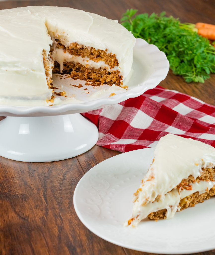 Homemade carrot cake frosted with cream cheese frosting on white cake platter.