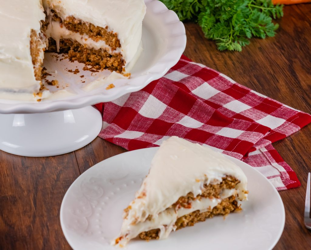 A slice fo carrot cake on a white plate with a red checkered napkin.