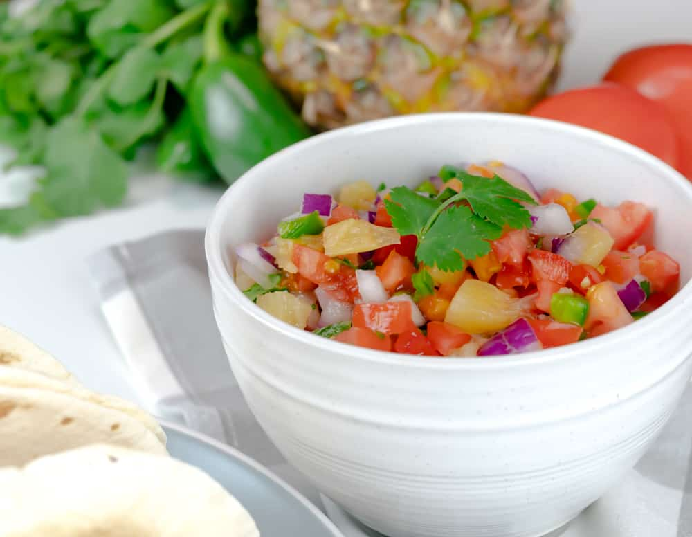 Pineapple Pico de Gallo served in a white bowl with fresh ingredients on a table.