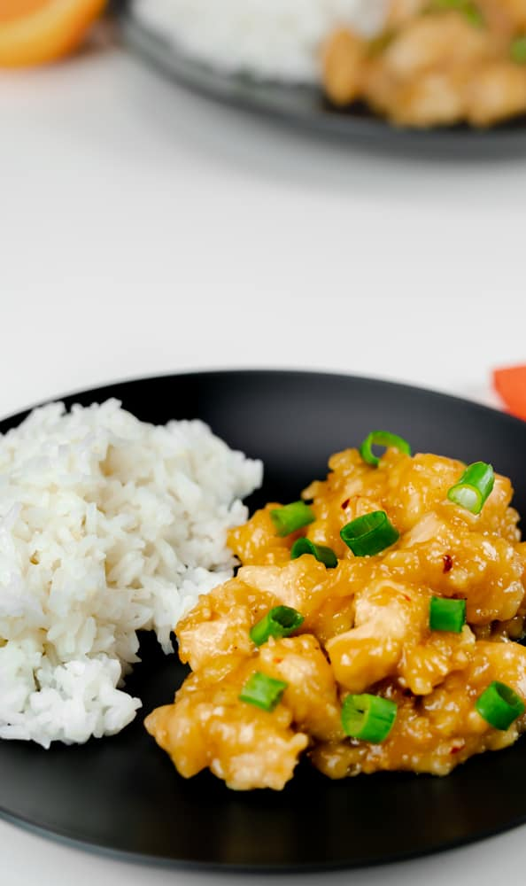 Instant Pot Orange Chicken Panda Express Copycat with green onions and white rice on black plate