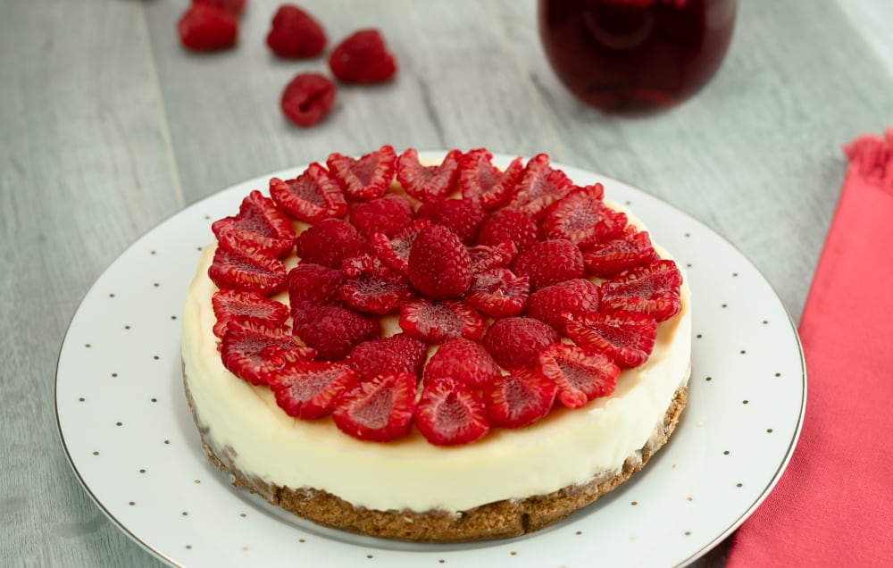Instant Pot Cheesecake with graham cracker crust and topped with freshly topped raspberries on white plate with polka dots and red napkin