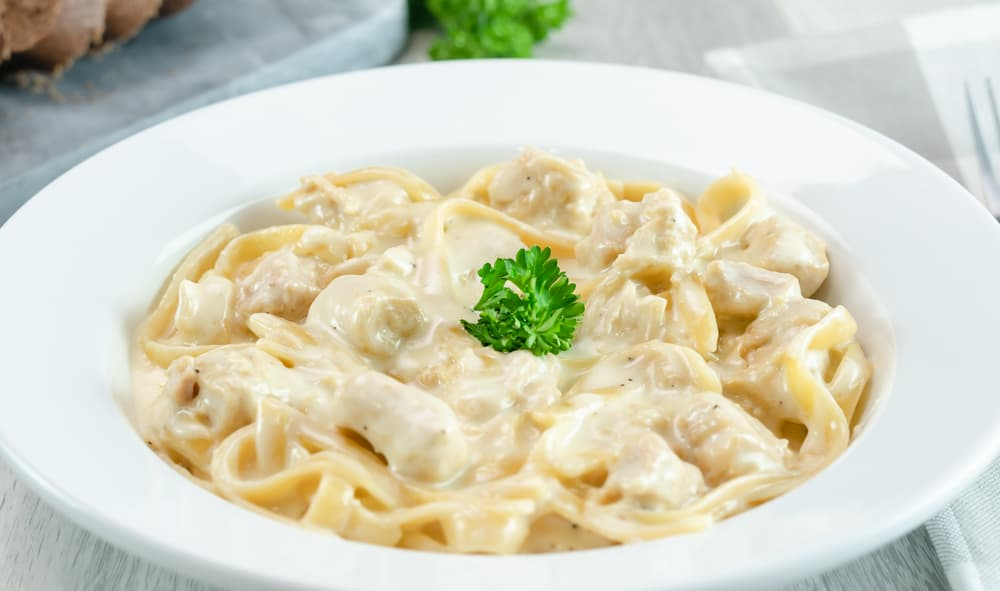 Instant Pot Chicken Alfredo Fettuccine Noodles with parsley garnishment on gray background.