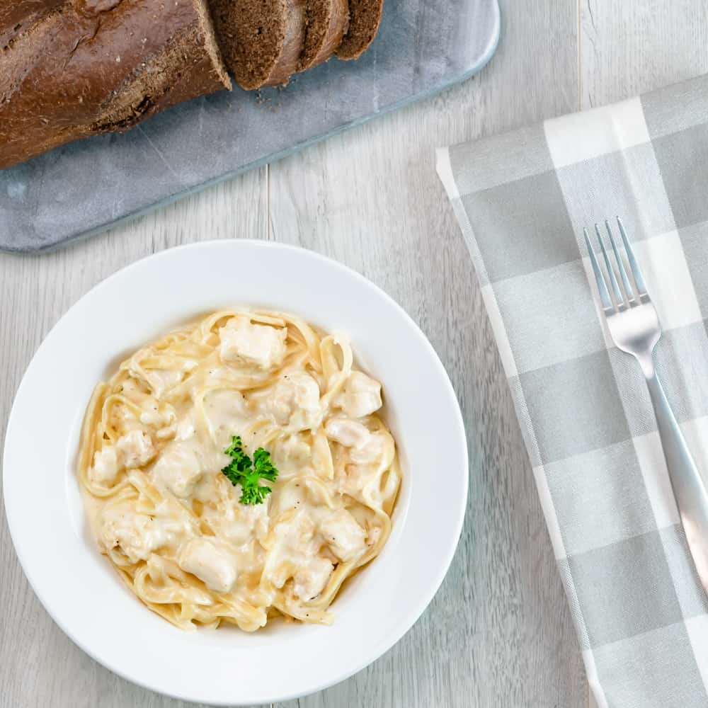 Instant Pot Chicken Alfredo Fettuccine Noodles with parsley garnishment and honey bread on gray background