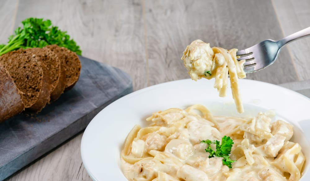 Instant Pot Chicken Alfredo Fettuccine Noodles with parsley garnishment and honey bread on gray background on fork.