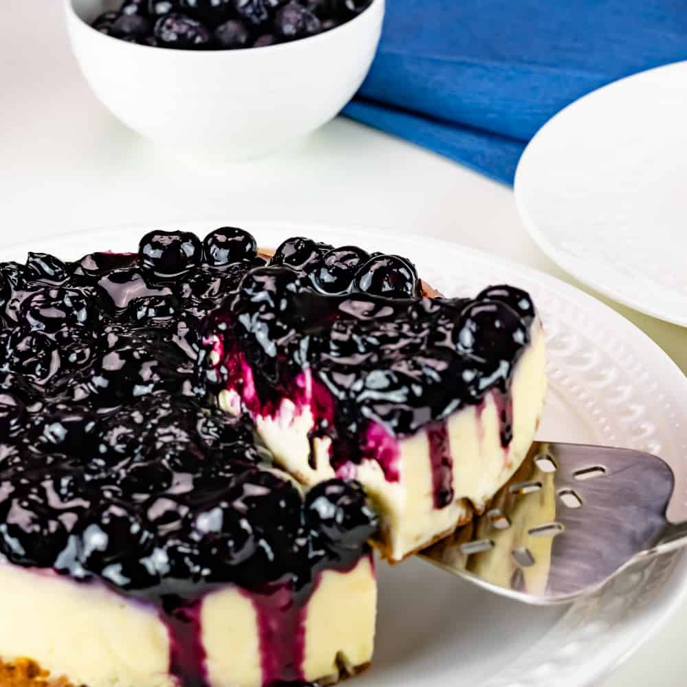 A slice taken out of Instant Pot Blueberry Cheesecake.