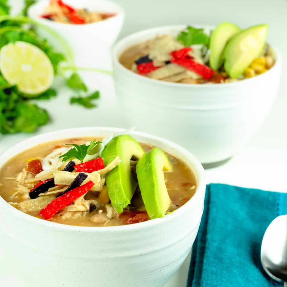 Instant Pot White Chicken Chili in white bowl and garnished with tricolor tortilla sticks, sliced avocado, cheese, and cilantro.