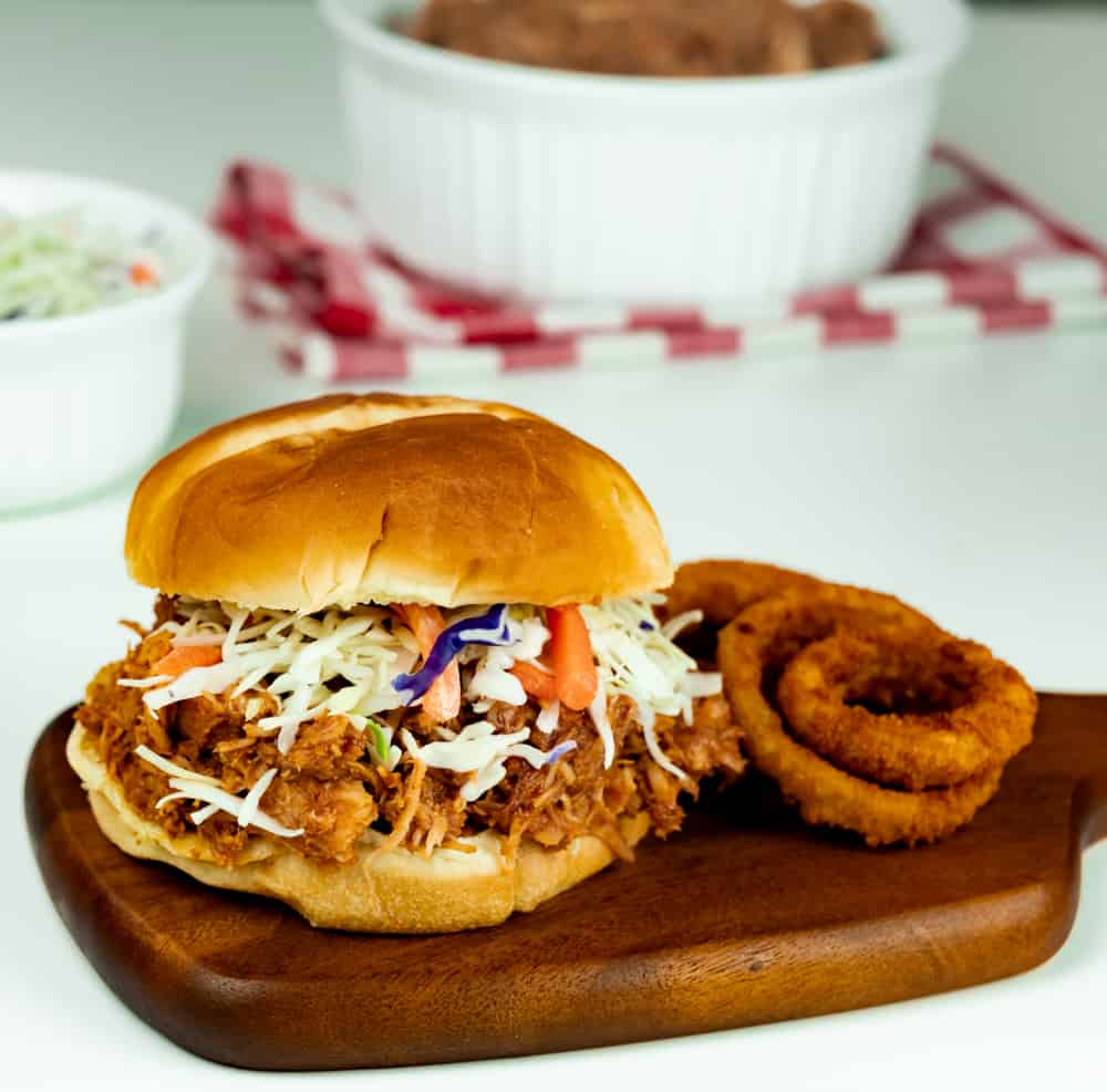 Instant Pot Sweet and Savory Pulled Pork served on a bun with onion rings.