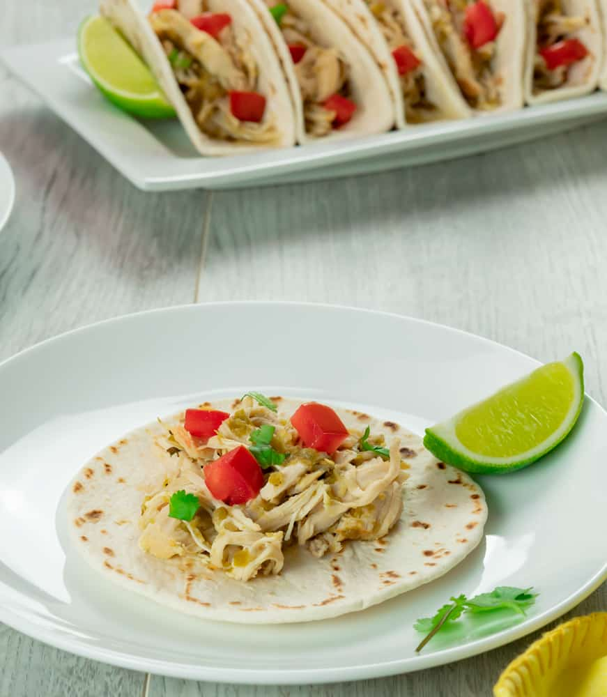 Instant Pot salsa verde chicken tacos with roma tomatoes, cilantro, and lime.