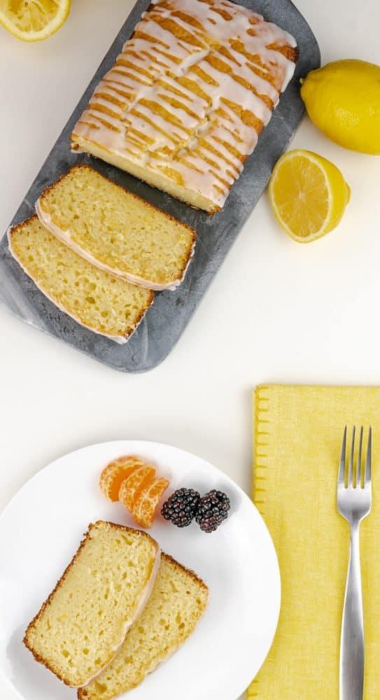 Lemon Loaf with Lemon Glaze with yellow napkin cut lemons and fork.
