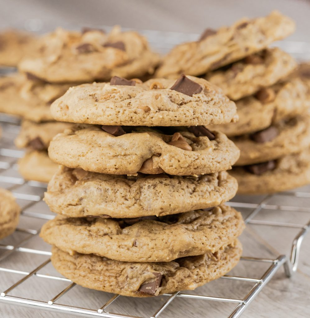 Chocolate chunk peanut butter cookies stacked on wire rack.