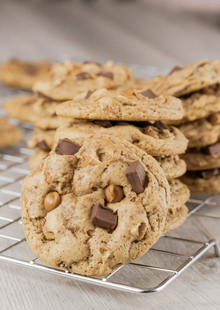 Large peanut butter chocolate chunk cookie propped on a stack of cookies.