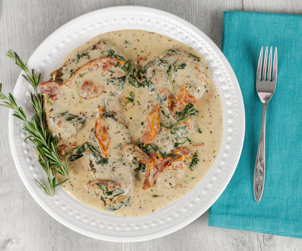 Instant Pot Creamy Tuscan Chicken served with fresh rosemary.