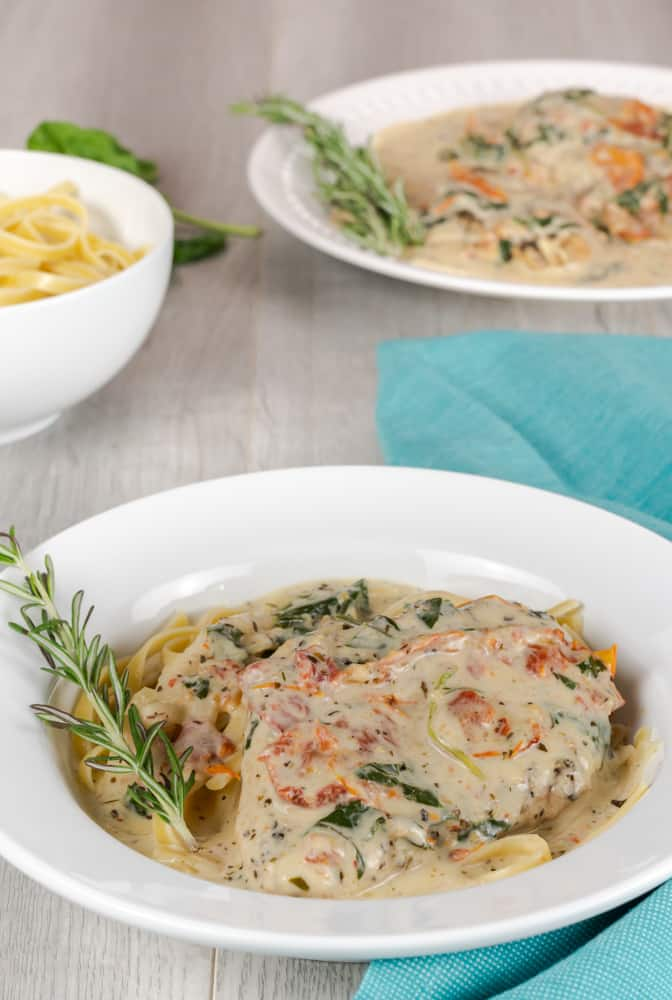 Instant Pot Creamy Tuscan Chicken served with fresh rosemary and fettuccine.