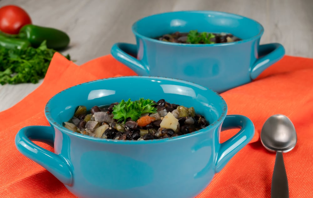 Two bowls of black bean soup that was made in the Instant Pot served in blue bowls with handles.