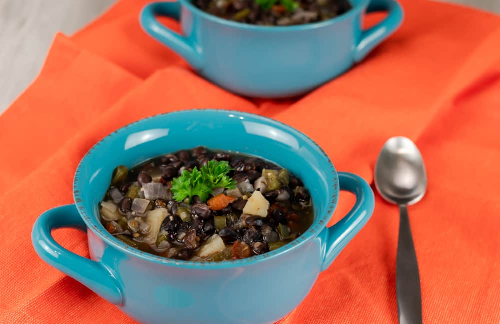 Instant Pot Caribbean Black Bean Soup in a blue bowl with a spoon.