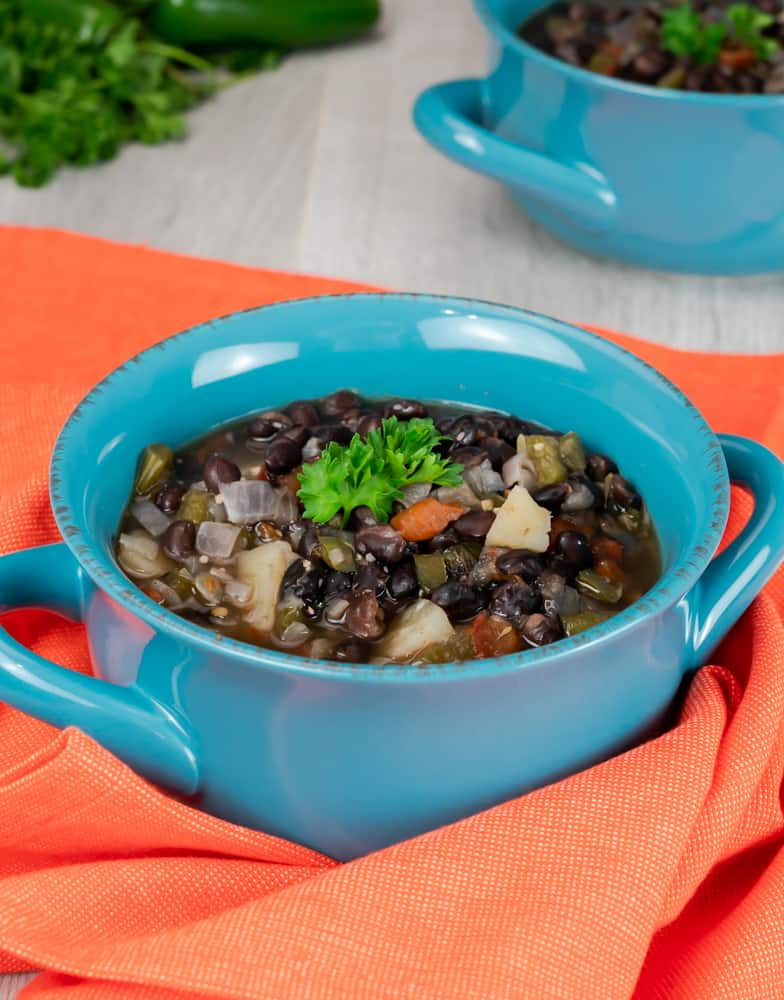 Instant Pot Caribbean Black Bean Soup served in a blue bowl with handles and garnished with parsley.