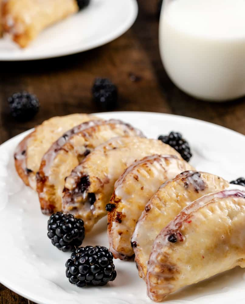 Fried Blackberry Hand Pies with a glaze served on a plate with fresh blackberries.