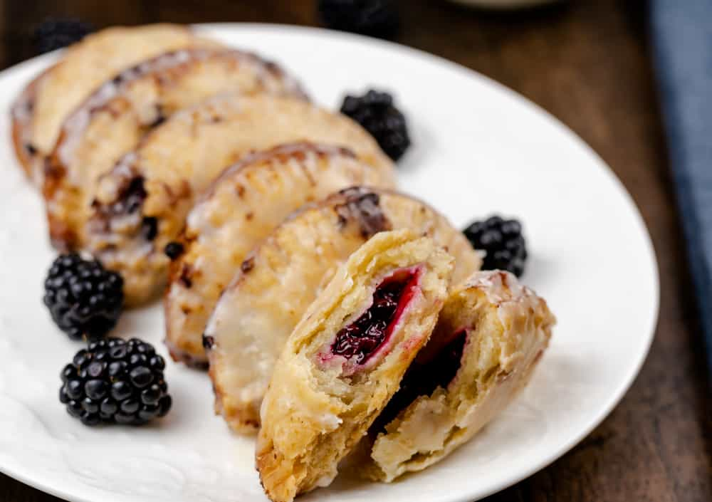 Fried Blackberry Pies with one broken in half to see the blackberry filling.