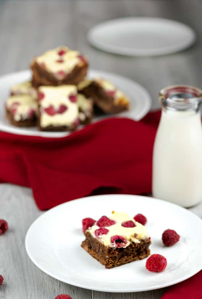 A single raspberry cheesecake brownie on a white plate with raspberries and a jar of milk.