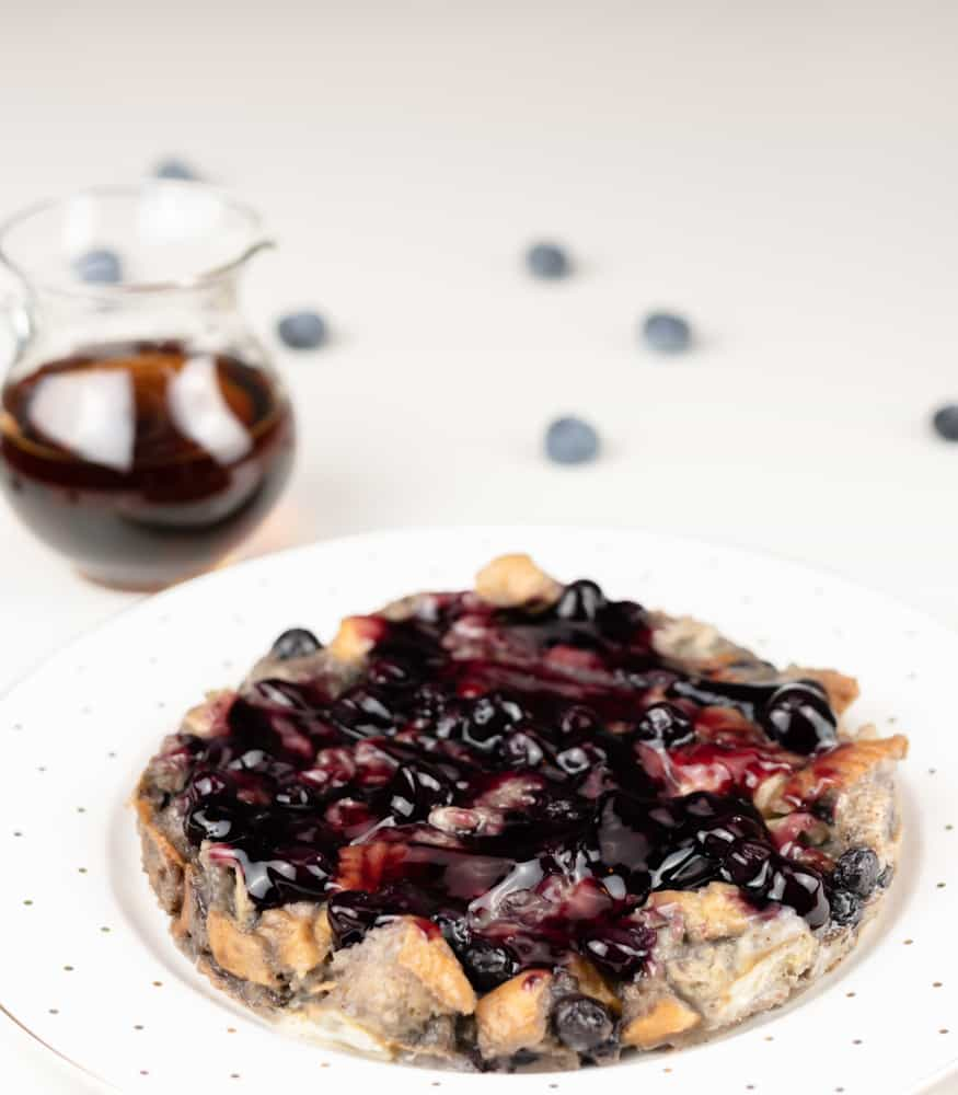Instant Pot blueberry French toast on a white serving plate topped with blueberries.