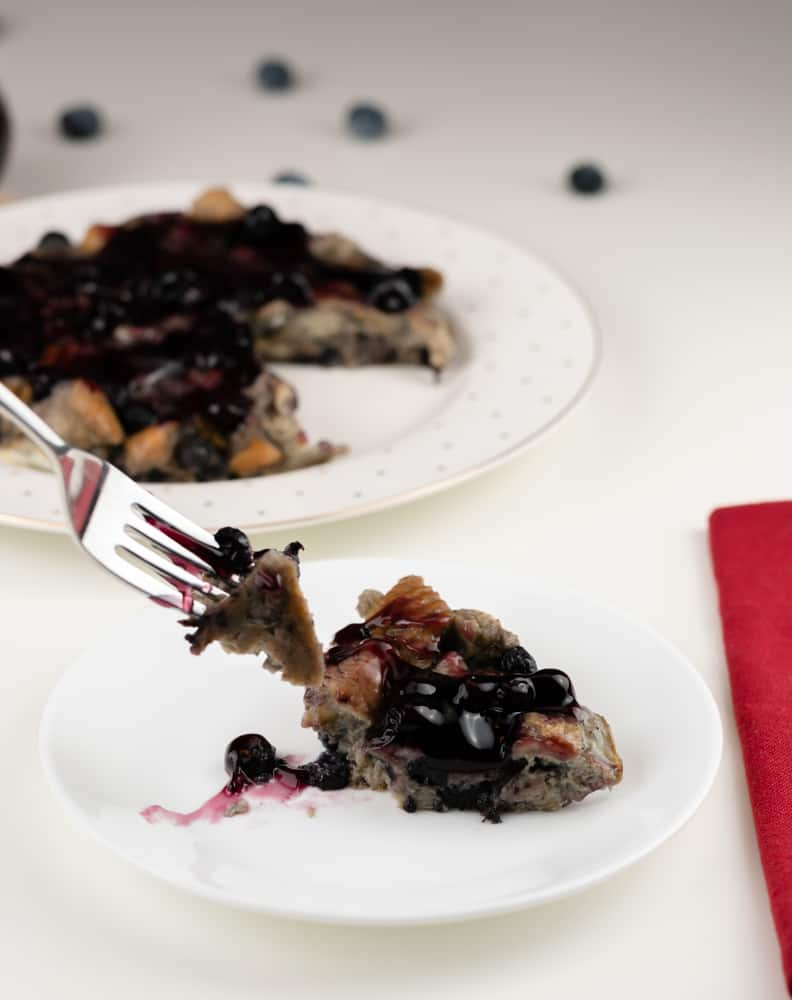 A fork of French toast with blueberries on a white plate with the French toast casserole in the background.