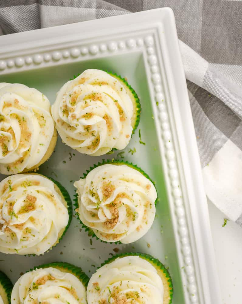 Key lime cupcakes in a green wrapper with key lime buttercream frosting garnished with graham cracker crumbs and lime zest.