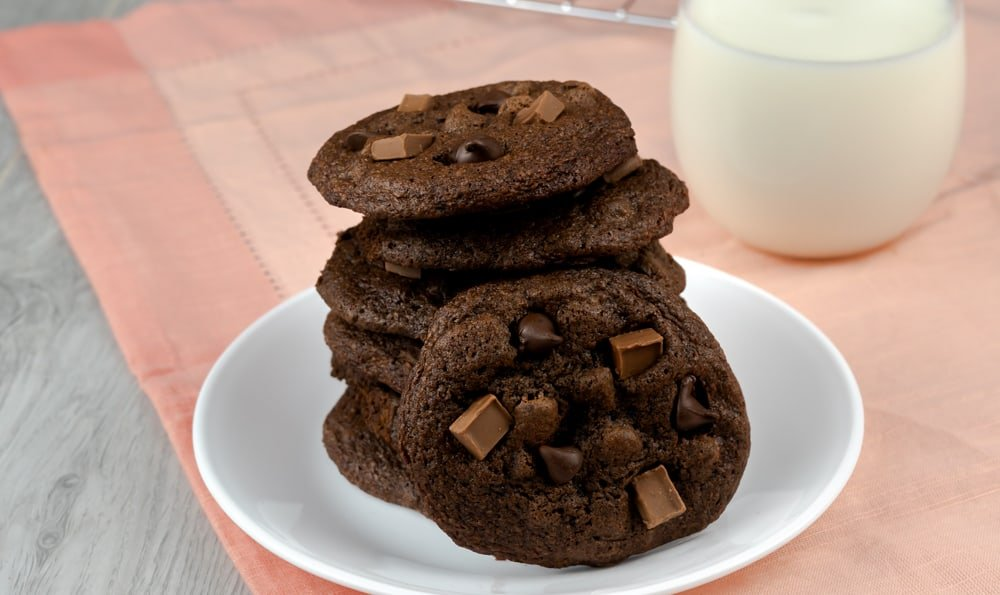 Chocolate chunk double chocolate cookies on a plate with a cookie propped in front of it.